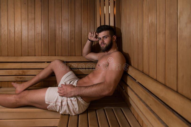 Reclinación atractiva del hombre relajada en sauna foto de archivo