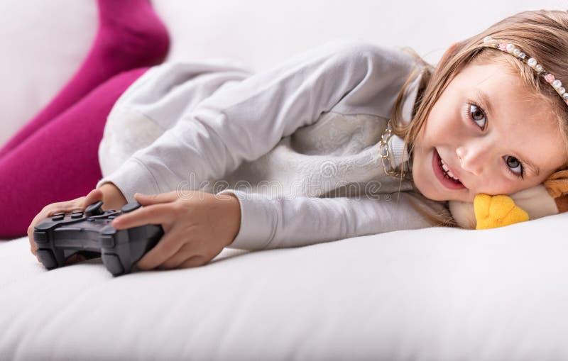 Reclinación de mentira de la niña bonita linda sobre su cama imagen de archivo