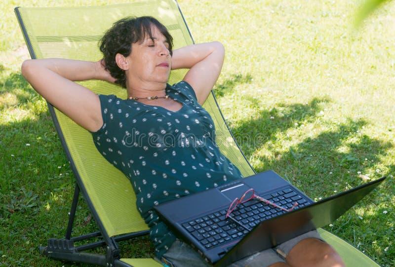 Reclinación de relajación de la mujer madura feliz sobre la silla de cubierta en jardín foto de archivo libre de regalías