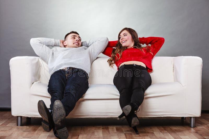 Reclinación de relajación de los pares felices sobre el sofá en casa fotos de archivo libres de regalías