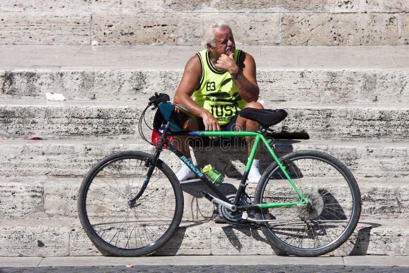 Reclinación del hombre y de la bici fotos de archivo