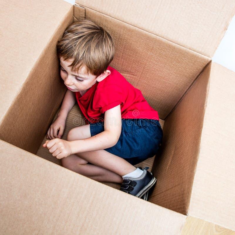 Reclinación linda del niño joven, jugando en la caja de cartón para la imaginación fotografía de archivo libre de regalías