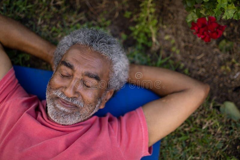 Reclinación masculina mayor con los ojos cerrados en la estera del ejercicio fotografía de archivo libre de regalías