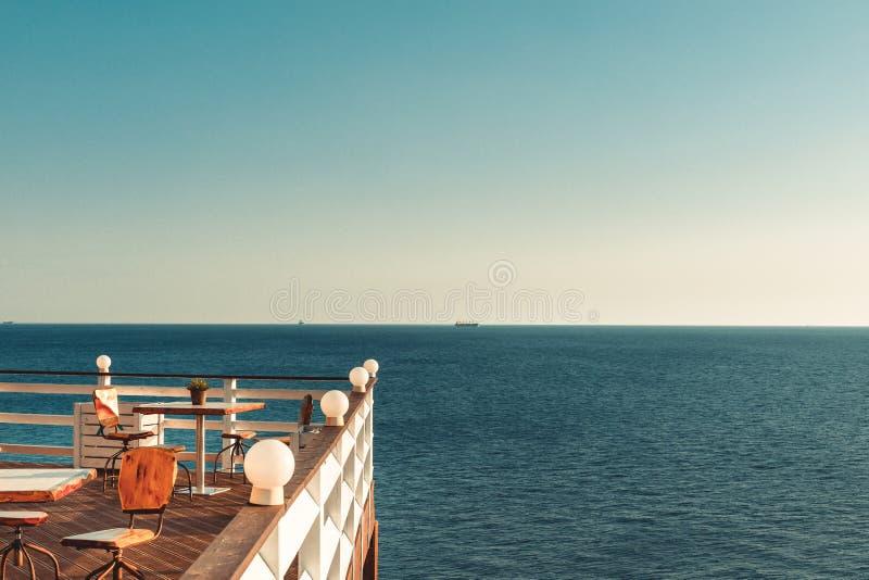Reclinación por el mar Tabla y sillas en un balcón de madera con a foto de archivo