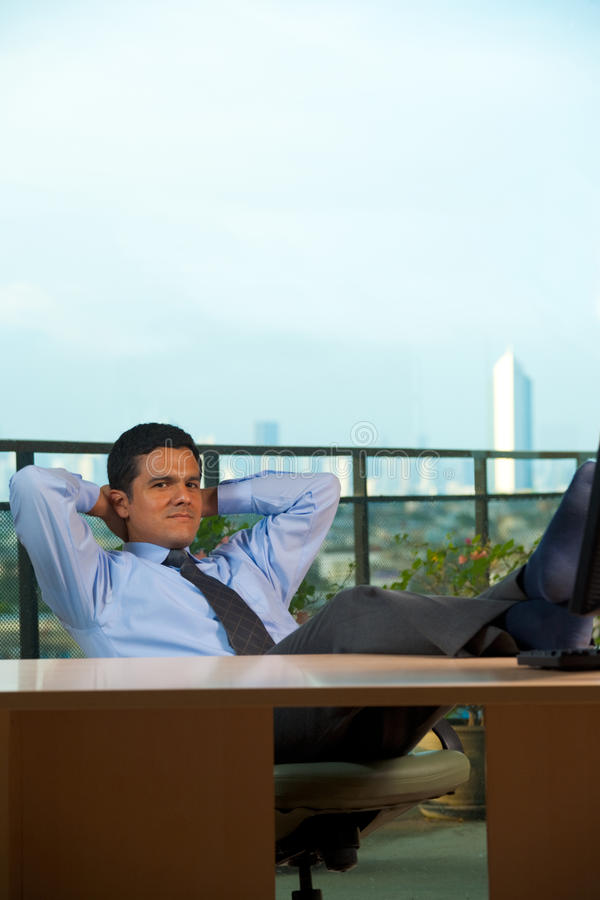 Reclined Hispanic Businessman Hand Behind Head royalty free stock images