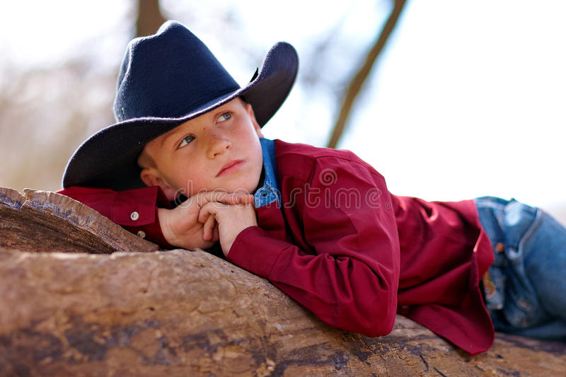 reclining barn för cowboy fotografering för bildbyråer