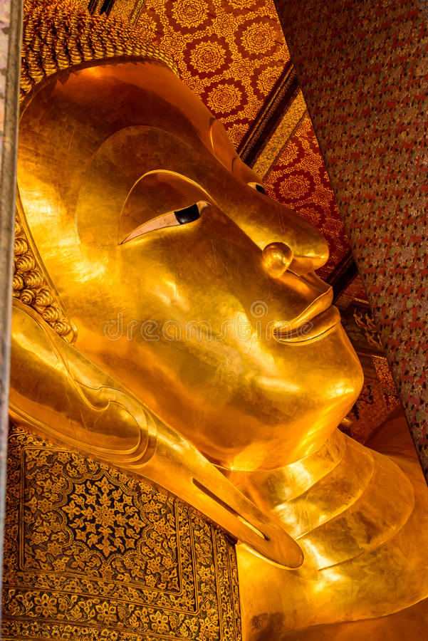 The reclining Buddha gold statue face in Bangkok, Thailand. stock photo