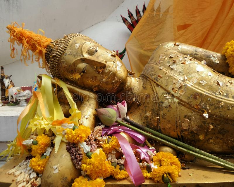 Reclining Buddha sculpture with gold leaves covered stock photography