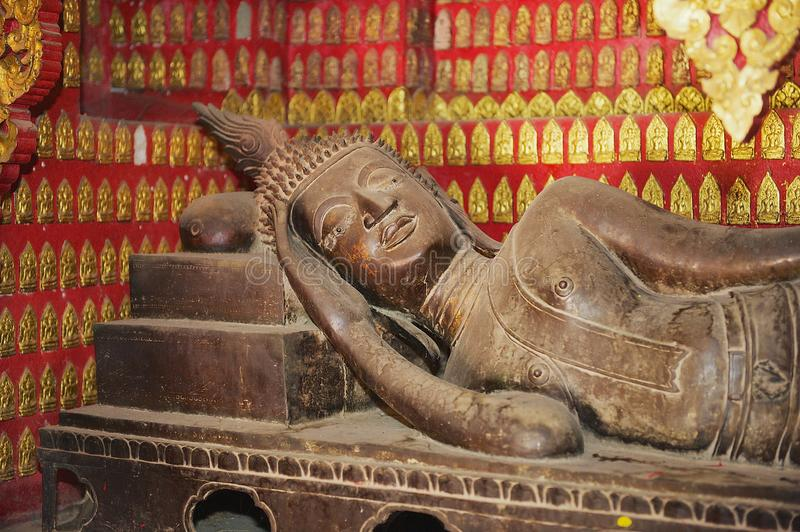 Reclining Buddha statue in a red chapel in Wat Xieng Thong temple in Luang Prabang, Laos. Reclining Buddha statue in a red chapel with many small Buddha statues royalty free stock photo