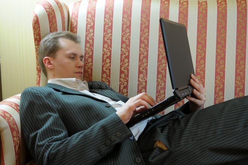 reclining för bärbar datorman royaltyfri fotografi