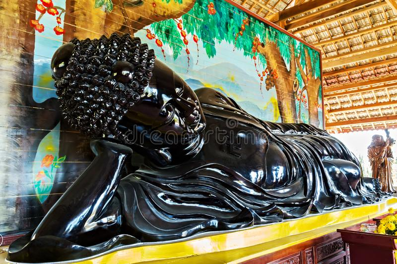 Reclining Sleep black buddha statues supporting his head with his hand Happy Bodhi day. Reclining Sleep black buddha statues supporting his head with his hand royalty free stock photography