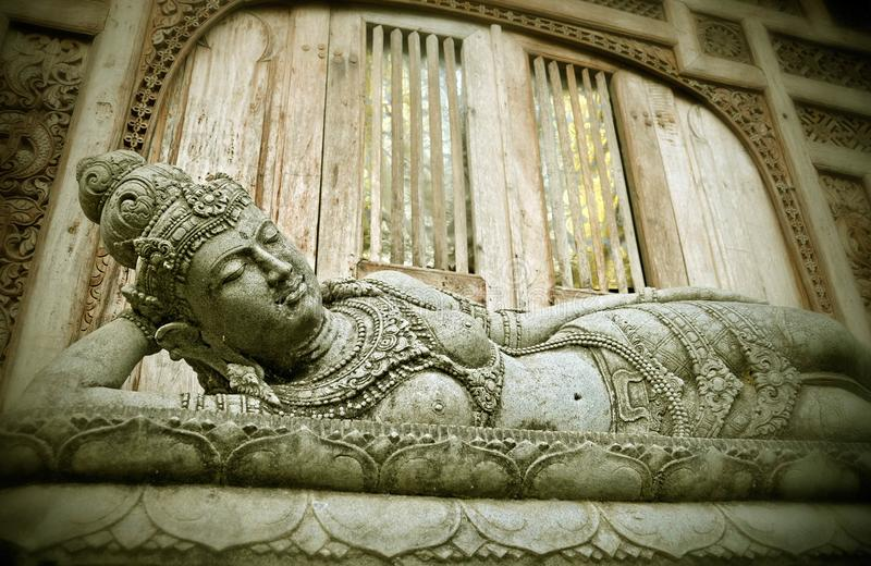 Reclining and sleeping Buddha Balinese religious statue in Ubud in the Island of Bali , Indonesia at the gate of temple in Buddhis stock images