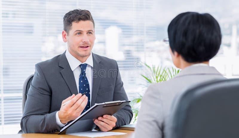 Reclutador que comprueba al candidato durante entrevista de trabajo imagen de archivo