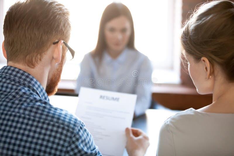 Reclutadores que leen el curriculum vitae femenino del candidato durante entrevista imagen de archivo