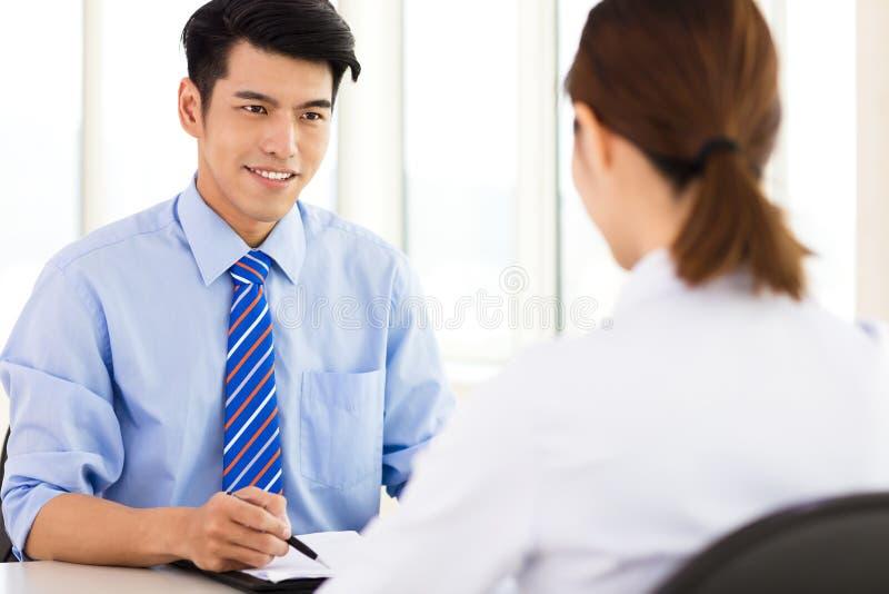 Reclutatore che controlla il candidato durante l'intervista di lavoro immagini stock libere da diritti