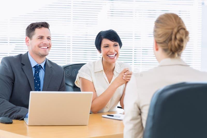 Reclutatori che controllano il candidato durante l'intervista di lavoro immagine stock libera da diritti