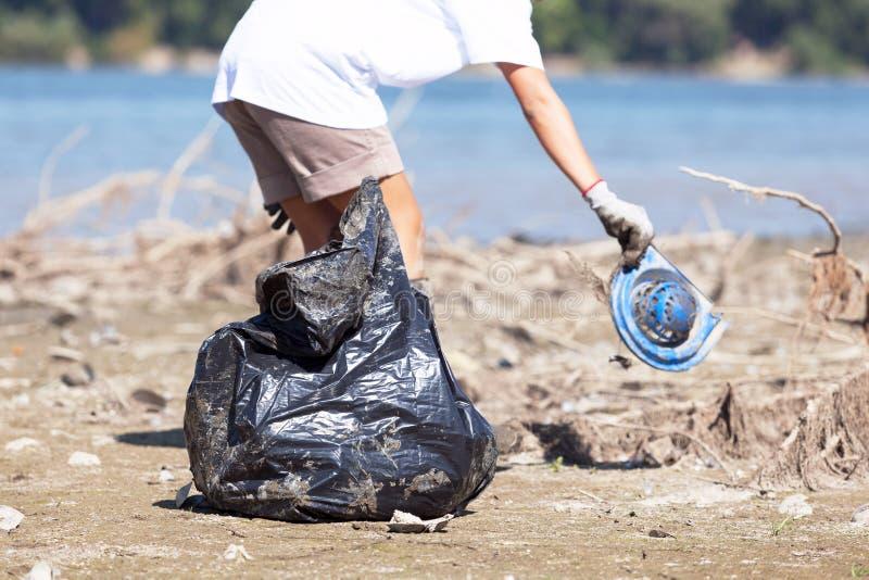Recogida de la basura plástica en la costa del río o del lago foto de archivo