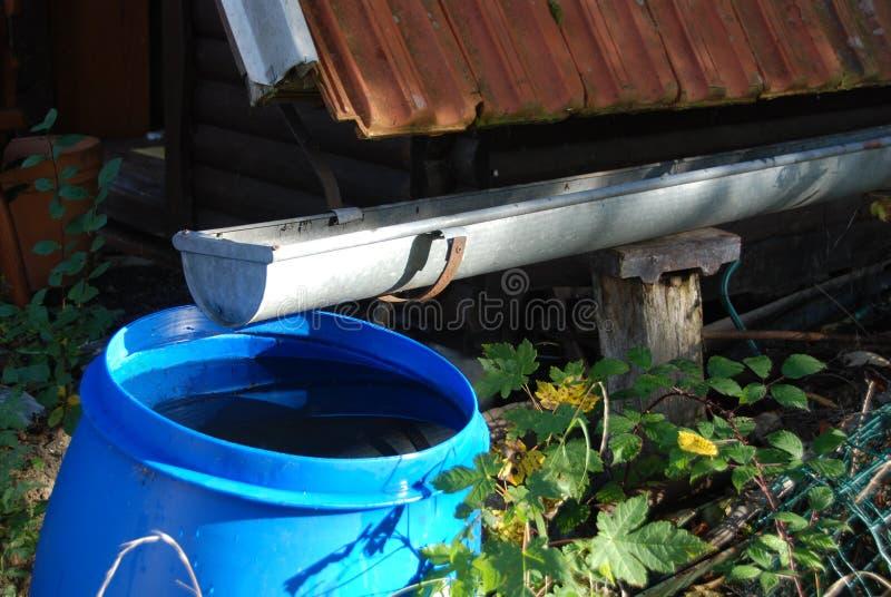 Recogiendo el agua de lluvia para regar el jardín foto de archivo libre de regalías