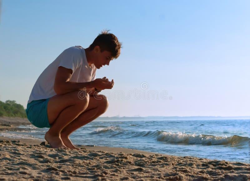 Recoja las piedras en la orilla de mar, el muchacho recoge piedras en el mar, el hombre joven que descansa sobre la costa de mar foto de archivo