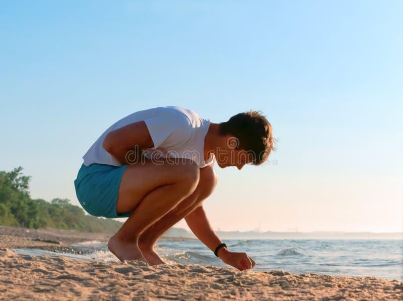 Recoja las piedras en la orilla de mar, el muchacho recoge piedras en el mar, el hombre joven que descansa sobre la costa de mar fotos de archivo