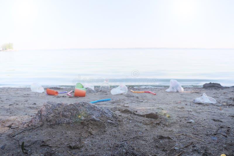 Recolección de basura en la playa Plástico y paquetes dispersados en la playa Un hombre recoge plástico Concepto de la protecci?n imagen de archivo