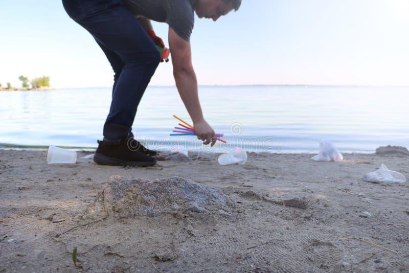 Recolha de lixo na praia Plástico e pacotes dispersados na praia Um homem recolhe plástico Conceito da prote??o da ecologia fotografia de stock royalty free