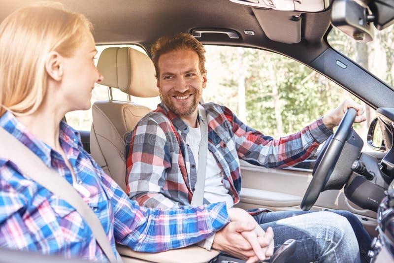 Recolha momentos, não coisas Pares novos que mantêm as mãos unidas no carro e que olham se Viagem por estrada da família imagens de stock royalty free