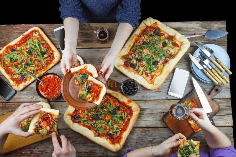 Recolhimentos amigáveis na tabela de jantar com pizza caseiro e cerveja escura foto de stock royalty free