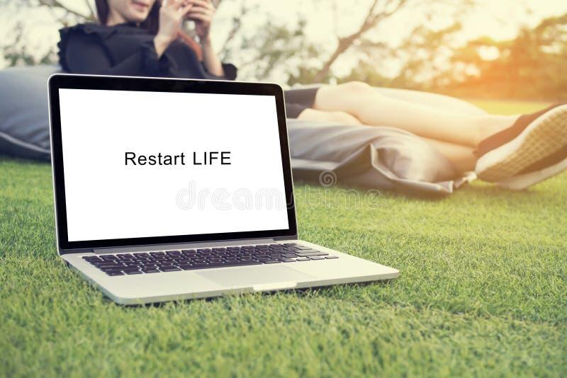 Recomience el texto de la vida en la pantalla del ordenador portátil con el asiático joven sonriente de la cara fotografía de archivo libre de regalías