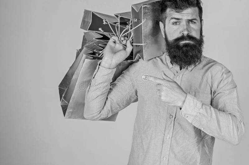 Recommendation concept. Guy shopping on sales season, pointing at bags. Hipster on serious face recommends to buy. Man. With beard and mustache carries bunch of royalty free stock photos
