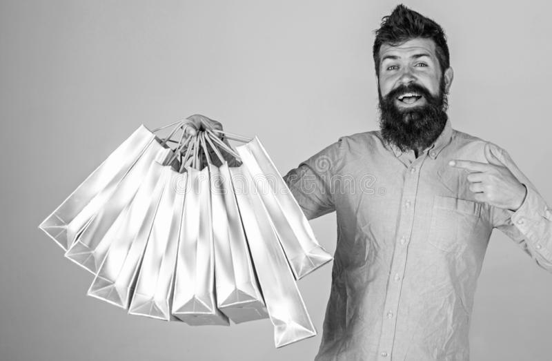 Recommendation concept. Guy shopping on sales season, pointing at bags. Hipster on smiling face recommends to buy. Man. With beard and mustache carries bunch of royalty free stock photos
