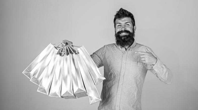 Recommendation concept. Hipster on smiling face recommends to buy. Guy shopping on sales season, pointing at bags. Man. With beard and mustache carries bunch of stock image