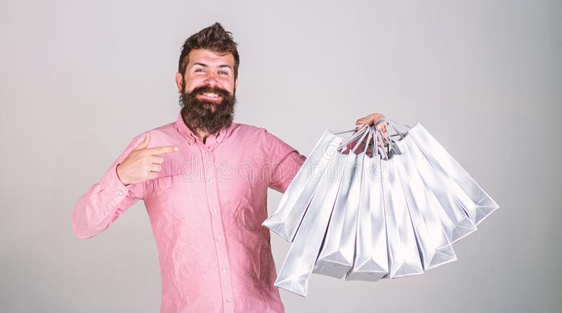 Recommendation concept. Hipster on smiling face recommends to buy. Guy shopping on sales season, pointing at bags. Man. With beard and mustache carries bunch of stock images