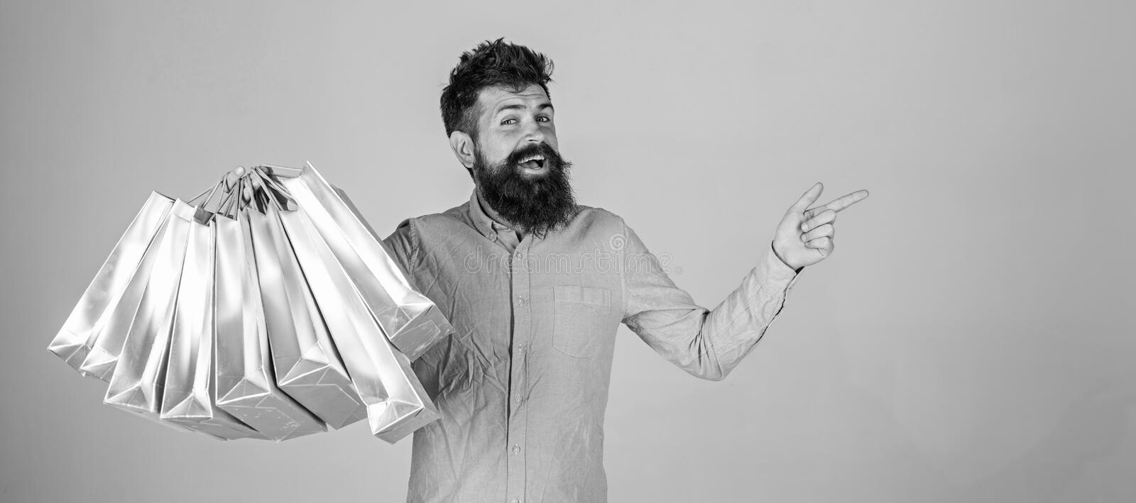Recommendation concept. Hipster on smiling face recommends to buy. Guy shopping on sales season, pointing at blank. Surface. Man with beard and mustache carries royalty free stock images
