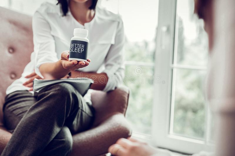 Therapist wearing grey trousers and white shirt recommending sleep pills. Recommending sleep pills. Therapist wearing grey trousers and white shirt sitting in royalty free stock image