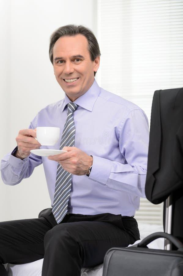 Reconstitution de son énergie. Coffe potable d'homme d'affaires mûr gai photo libre de droits