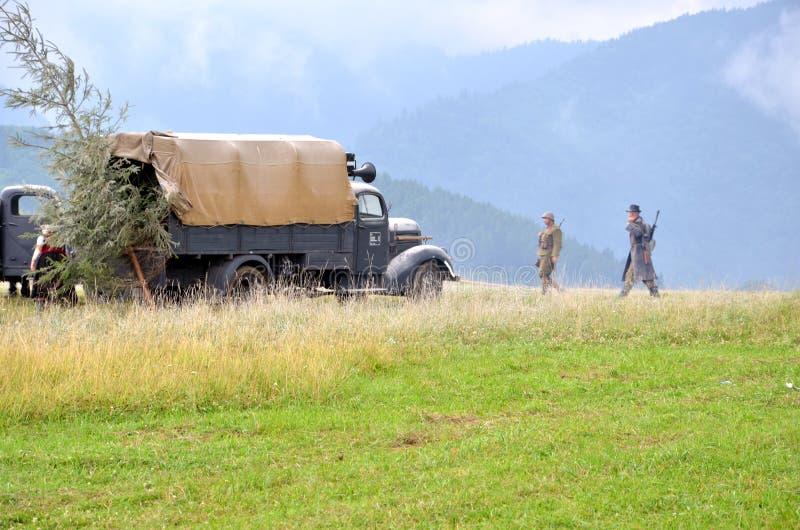 Reconstitution historique de bataille de la guerre mondiale 2 - le véhicule et les soldats de transport blindés se sont habillés  photographie stock libre de droits