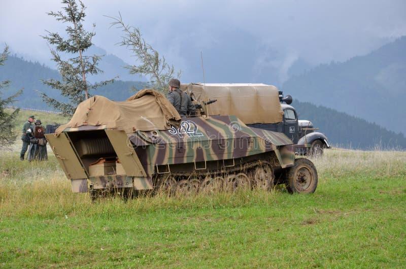 Reconstitution historique de bataille de la guerre mondiale 2 - le véhicule et les soldats de transport blindés se sont habillés  images libres de droits
