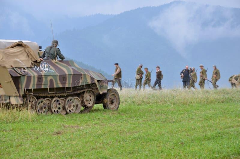 Reconstitution historique de bataille de la guerre mondiale 2 - le véhicule et les soldats de transport blindés se sont habillés  image libre de droits