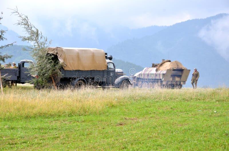 Reconstitution historique de bataille de la guerre mondiale 2 - le véhicule et les soldats de transport blindés se sont habillés  image stock