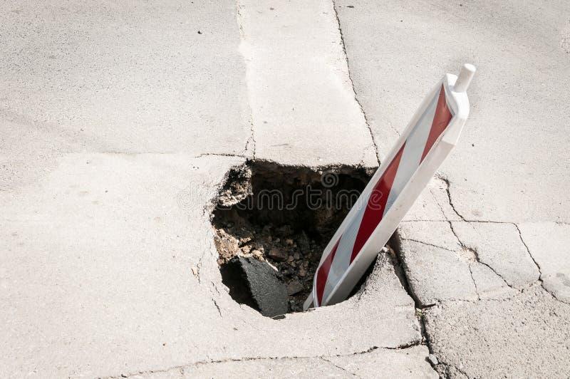Reconstrução da rua ou tampa do sinal do cuidado do perigo do tráfego da barricada da construção o furo aberto do asfalto sobre d imagem de stock royalty free