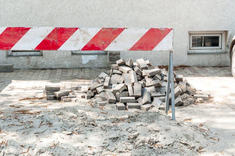 Reconstrução do parque de estacionamento na frente da construção residencial com tráfego ou barreira da estrada e da pilha da are fotos de stock royalty free