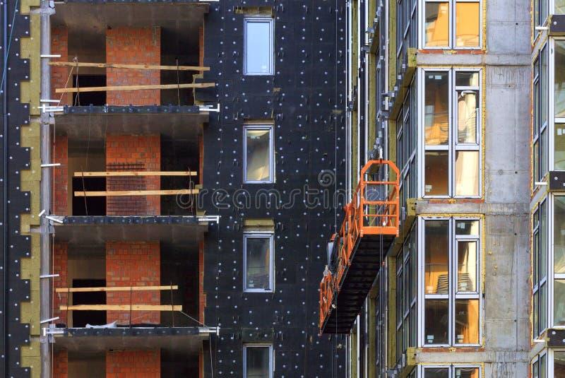 Reconstrução, isolação da fachada e a inserção de grandes quadros de janela em uma construção residencial moderna fotos de stock royalty free