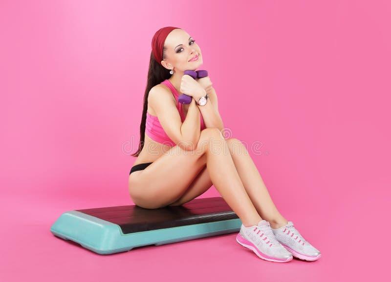 reconstrucción Mujer tranquila delgada con las pesas de gimnasia que se relajan fotografía de archivo