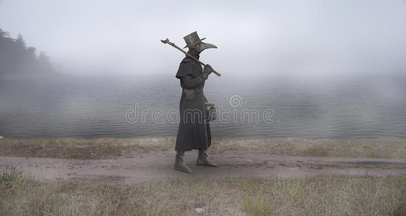Reconstruction of the medieval scene: the plague doctor on the w. Medieval era. The plague doctor walks along the road near the misty lake stock image