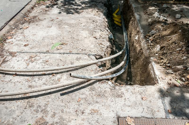 Reconstruction site with trench for underground telephone optical lines stock photography