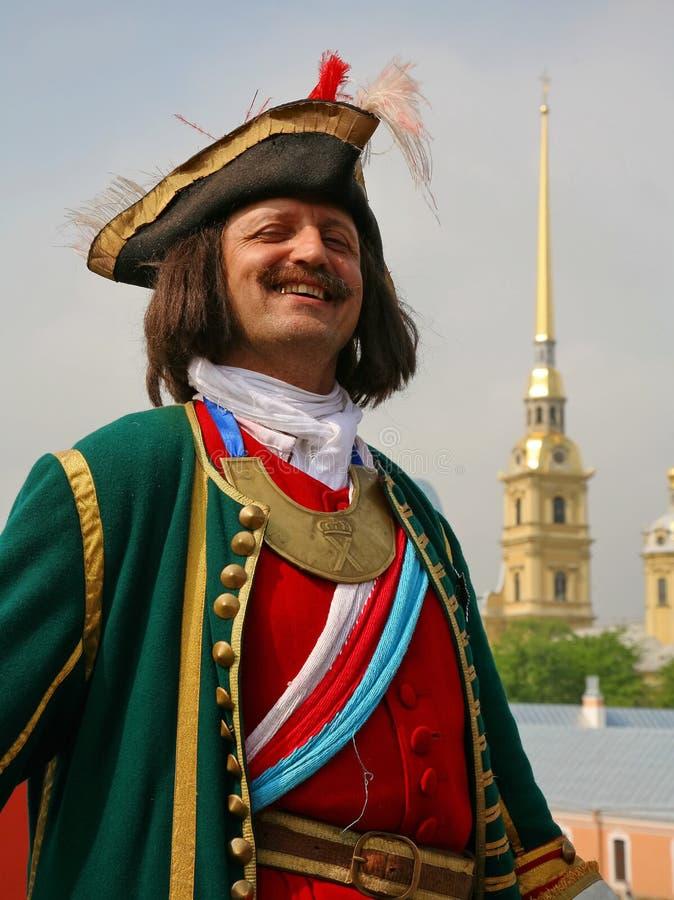Reconstructor in militair kostuum vanaf de 18de eeuw de achtergrond de spits van Peter en Paul Cathedral stock foto's