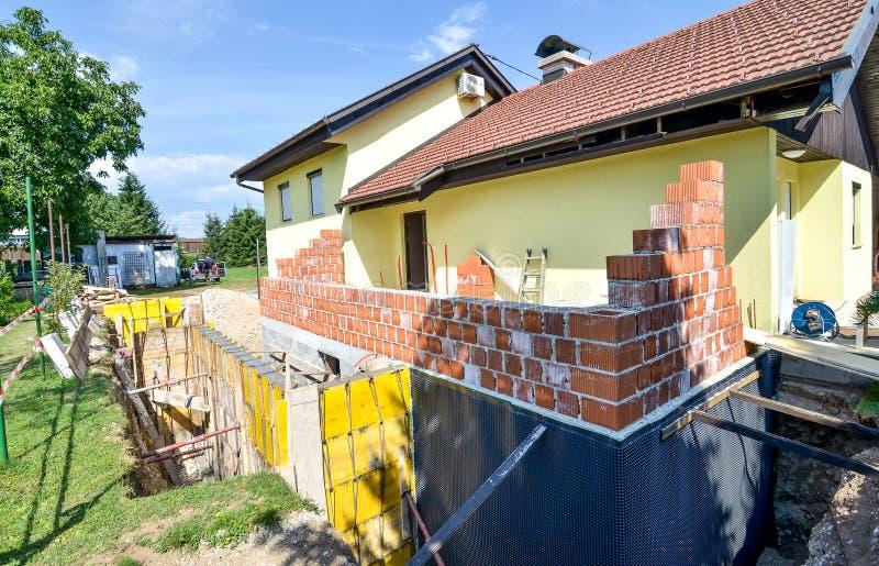 Reconstruindo uma casa e uma adição da família de uma extensão foto de stock