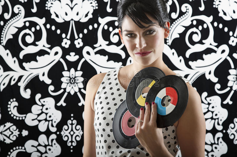 Record fan. Young woman is stylist 60's inspired clothing, holding three vinyl records in a fan position royalty free stock images