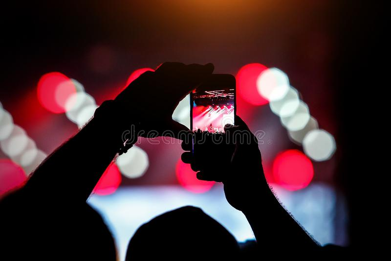 Record on a mobile phone of a concert, show. Holds a smartphone in hands royalty free stock photos